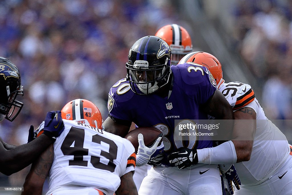 Bernard Pierce #30 of the Baltimore Ravens is tackled by Billy Winn #90 of the Cleveland Browns during the fourth quarter of a game at M&T Bank Stadium on September 15, 2013 in Baltimore, Maryland.