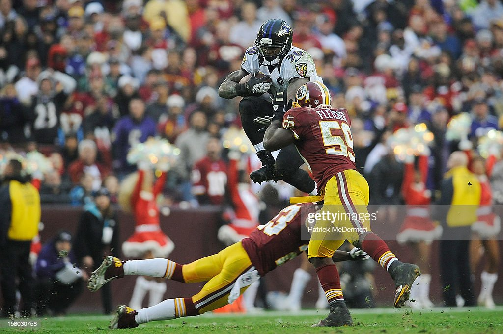 Bernard Pierce #30 of the Baltimore Ravens leaps to avoid the tackle of DeAngelo Hall #23 and London Fletcher #59 of the Washington Redskins during a game at FedExField on December 9, 2012 in Landover, Maryland.