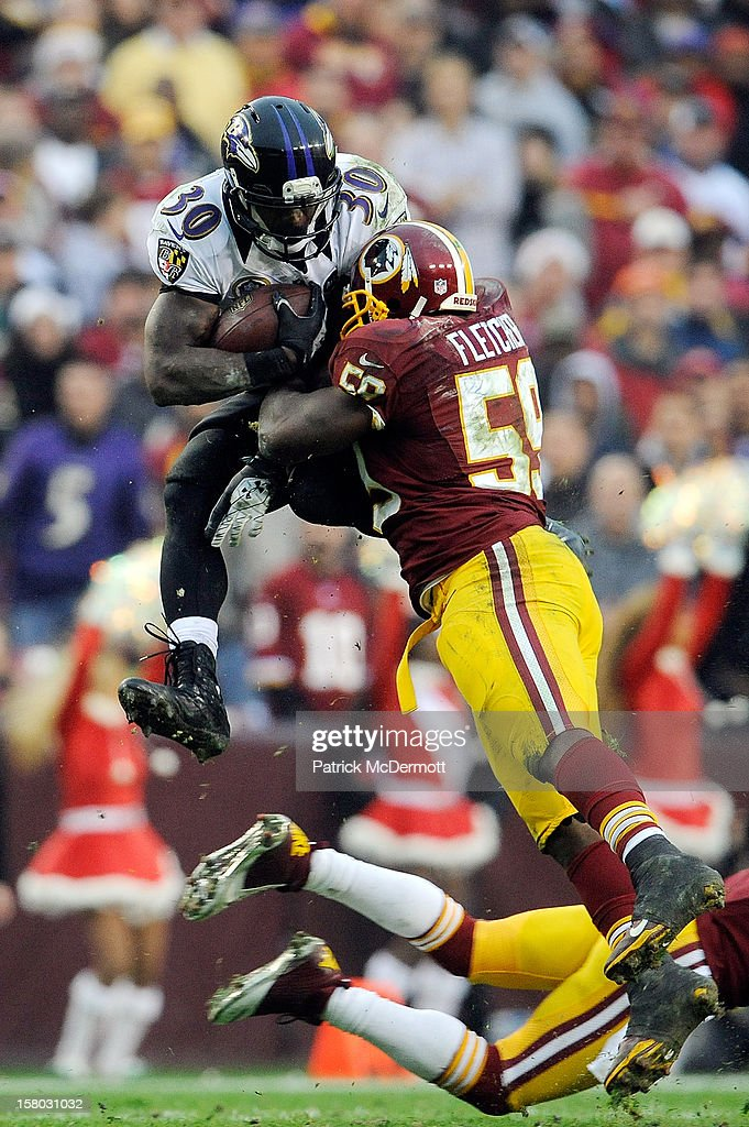Bernard Pierce #30 of the Baltimore Ravens leaps to avoid the tackle of DeAngelo Hall #23 and <a gi-track='captionPersonalityLinkClicked' href=/galleries/search?phrase=London+Fletcher&family=editorial&specificpeople=223941 ng-click='$event.stopPropagation()'>London Fletcher</a> #59 of the Washington Redskins during a game at FedExField on December 9, 2012 in Landover, Maryland.