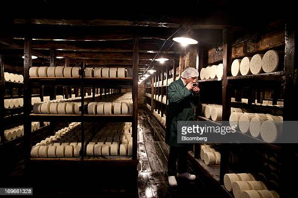 Bernard Roques a technician tests a sample of maturing Roquefort Societe 150years cheese in caves at the LebrouRoquefort plant part of Groupe...