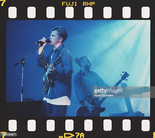 Bernard Sumner and Peter Hook performing with English rock group New Order circa 1990