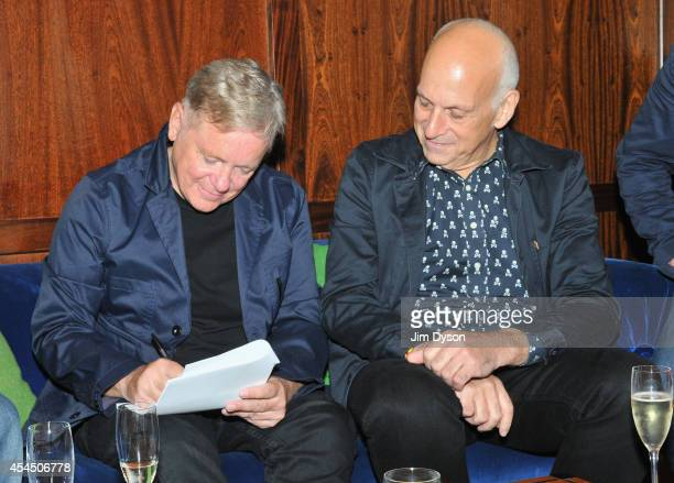 Bernard Sumner of New Order signs a new record deal with Mute Records as label founder Daniel Miller looks on at The Groucho Club on September 2 2014...