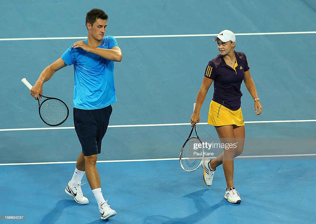 Bernard Tomic and Ashleigh Barty of Australia walk back to their seats in the mixed doubles match against Francesca Schiavone and Andreas Seppi of Italy during day six of the Hopman Cup at Perth Arena on January 3, 2013 in Perth, Australia.