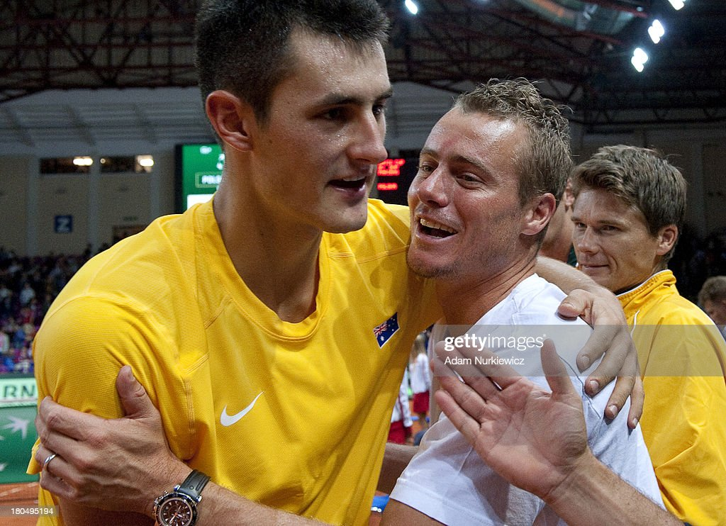 Bernard Tomic (L) and Lleyton Hewitt (R) of Australia celebrate after winning the second match during the Davis Cup match between Poland and Australia at the Torwar Hall, on September 13, 2013 in Warsaw, England.