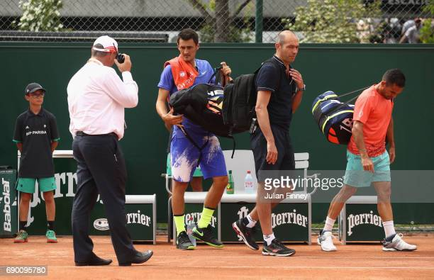 Bernard Tomic of Australia and partner Victor Estrella Burgos of The Dominican Republic look dejected leaving the leave the court following an injury...