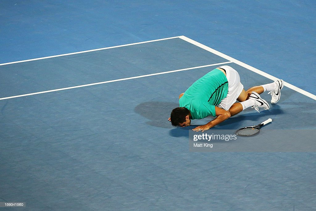 Bernard Tomic of Australia celebrates winning match point and kisses the court in the men's final match against Kevin Anderson of South Africa during day seven of the Sydney International at Sydney Olympic Park Tennis Centre on January 12, 2013 in Sydney, Australia.
