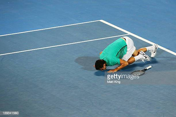 Bernard Tomic of Australia celebrates winning match point and kisses the court in the men's final match against Kevin Anderson of South Africa during...