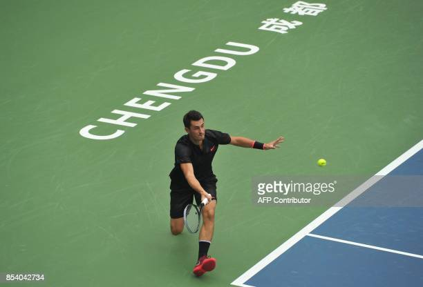 Bernard Tomic of Australia hits a return against Kyle Edmund of Britain during their men's singles first round match at the ATP Chengdu Open tennis...