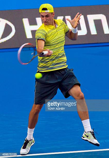 Bernard Tomic of Australia hits a return against Milos Raonic of Canada during their second session men's singles match on day one of the Hopman Cup...