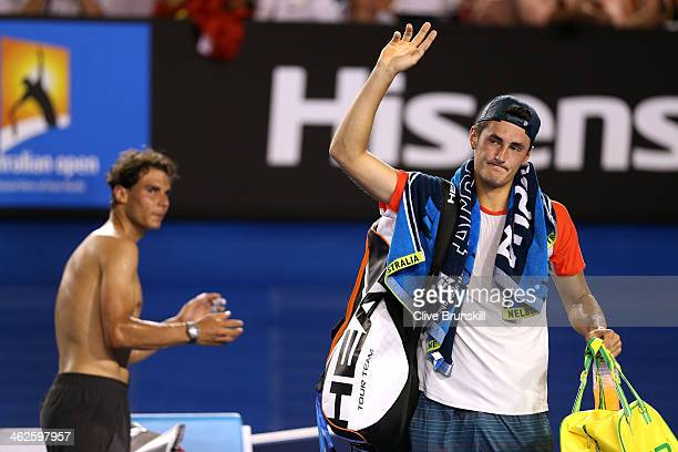 Bernard Tomic of Australia leaves the court as Rafael Nadal of Spain claps after Tomic retired from their first round match during day two of the...