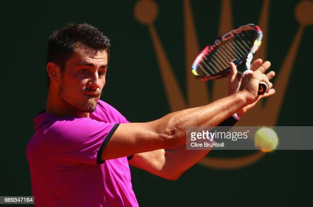 Bernard Tomic of Australia plays a backhand against Diego Schwartzman of Agentina during his straight sets defeat in his first round match on day two...