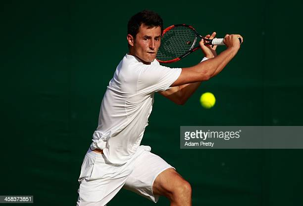 Bernard Tomic of Australia plays a backhand during the Men's Singles third round match against Roberto Bautista Agut of Spain on day six of the...