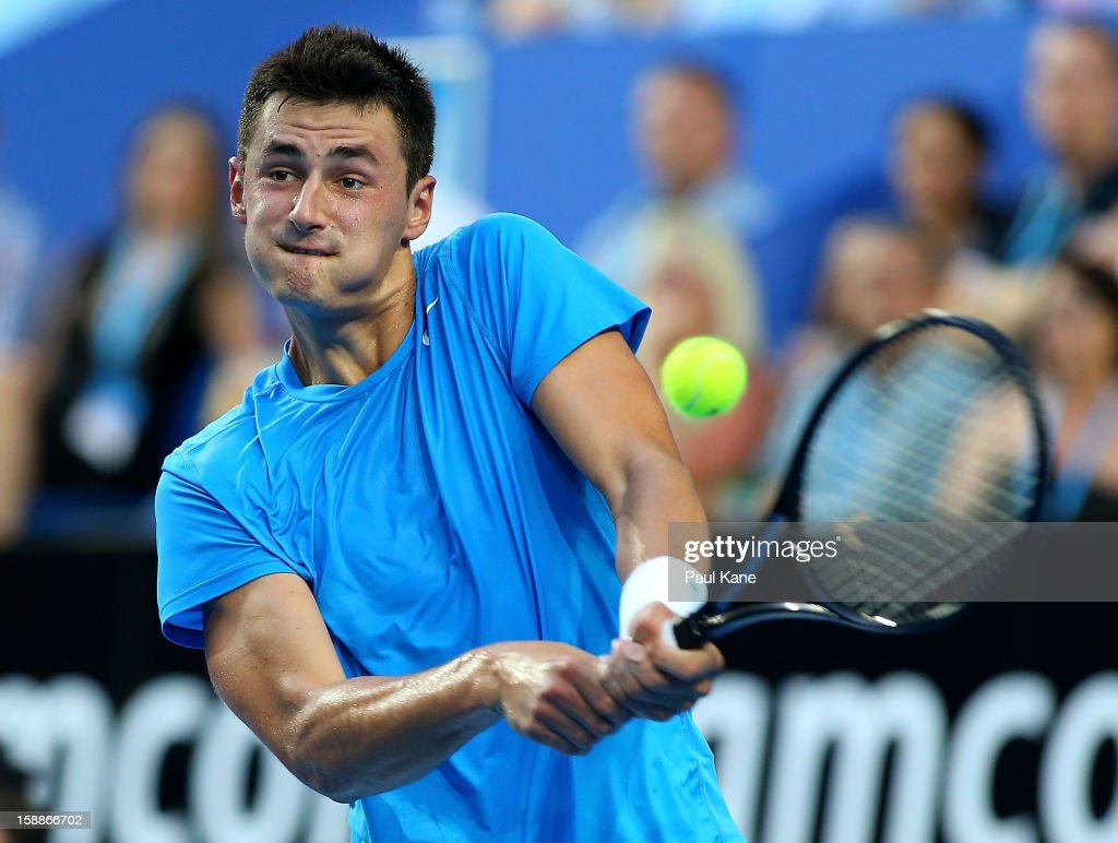 Bernard Tomic of Australia plays a backhand in his singles match against Novak Djokovic of Serbia during day five of the Hopman Cup at Perth Arena on January 2, 2013 in Perth, Australia.