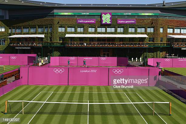 Bernard Tomic of Australia practices on outside courts during previews ahead of the 2012 London Olympic Games at the All England Lawn Tennis and...