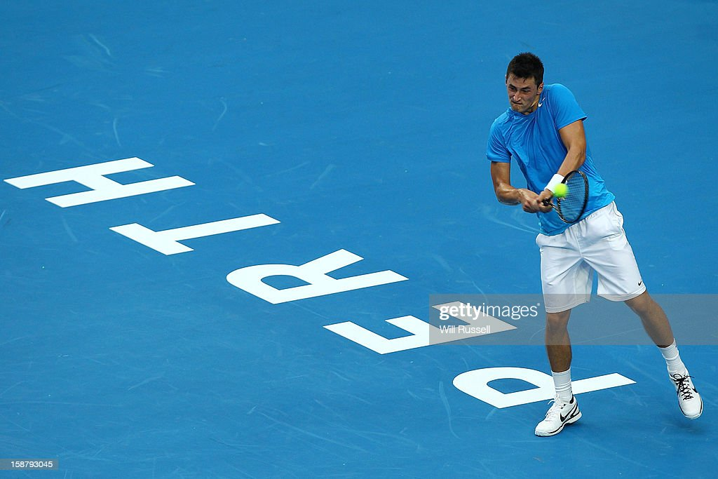 Bernard Tomic of Australia returns a backhand volley in his singles match against Tommy Haas of Germany during day one of the Hopman Cup at Perth Arena on December 29, 2012 in Perth, Australia.