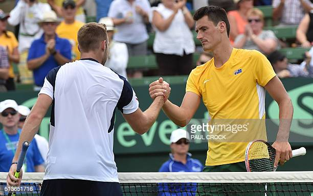 Bernard Tomic of Australia shakes hands with Jack Sock of the US after winning their men's singles match at the World Group first round Davis Cup...