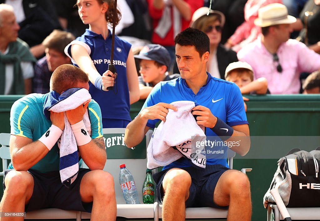 Bernard Tomic of Australia (r) talks with Sam Groth of Australia during the Men's Double first round match against Pierre-Hugues Herbert and Nicolas Mahut of France on day four of the 2016 French Open at Roland Garros on May 25, 2016 in Paris, France.