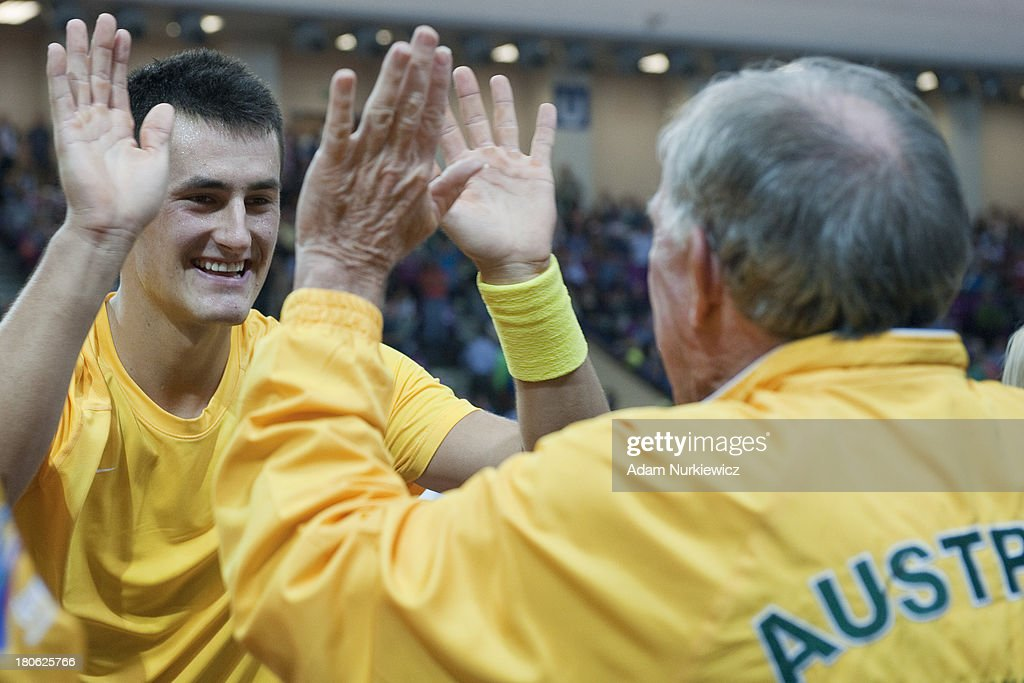 Bernard Tomic & (R) Tony Roche both from Australia celebrate winning game and victory in the Davis Cup match between Poland and Australia at the Torwar Hall, on September 15, 2013 in Warsaw, Poland.