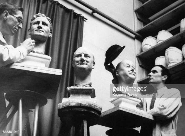 Bernard Tussaud travaille sur un buste de l'acteur Spencer Tracey pendant que son assistant s'amuse avec le chapeau de la tête en cire de l'humoriste...
