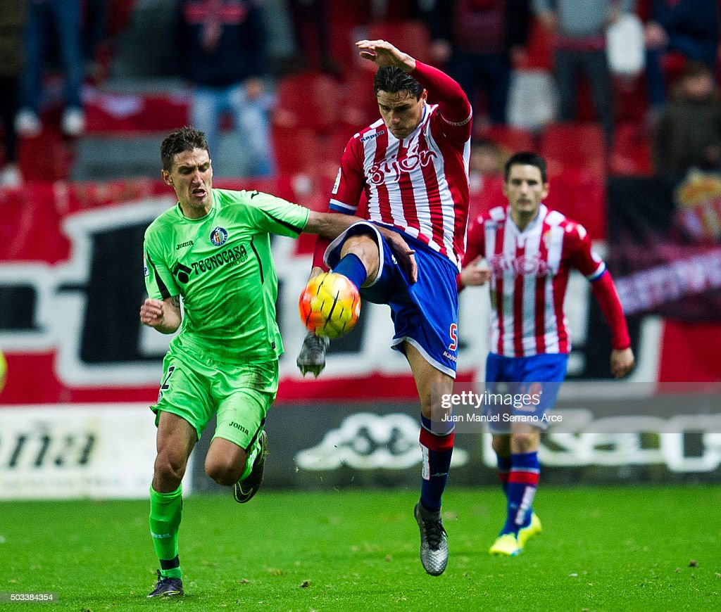 Bernardo Espinosa of Real Sporting de Gijon duels for the ball with Stefan Scepovic of Getafe CF during the La Liga match between Real Sporting de Gijon and Getafe CF at Estadio El Molinon on January 4, 2016 in Gijon, Spain.