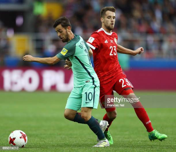 Bernardo Silva of Portugal and Dmitry Kombarov of Russia battle for possession during the FIFA Confederations Cup Russia 2017 Group A match between...