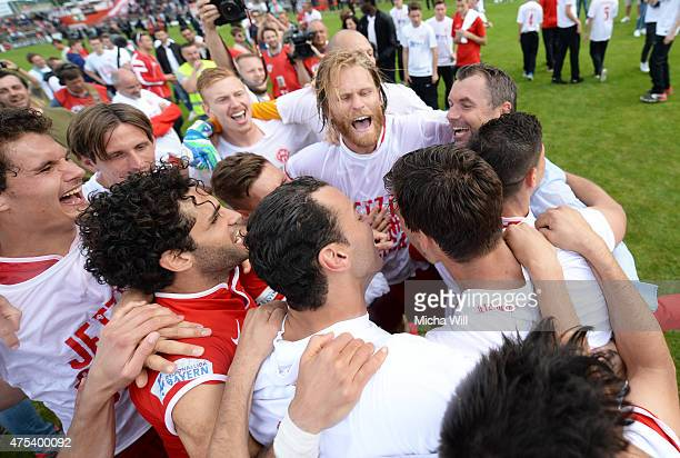 Bernd Hollerbach head coach of Wuerzburg celebrates his teams promotion to the third league with his players after the Regionalliga Playoffs match...