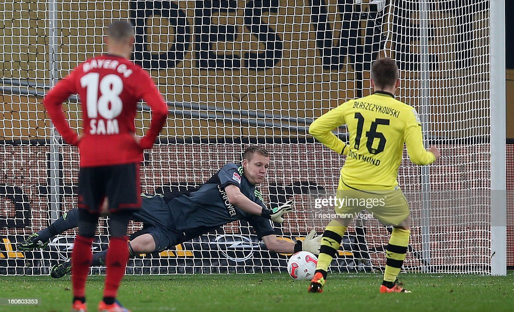 Bernd Leno (C) of Leverkusen saves the penalty from Jakub Kuba Blaszczykowski (R) of Dortmund battle for the ball during the Bundesliga match between Bayer 04 Leverkusen and Borussia Dortmund at BayArena on February 3, 2013 in Leverkusen, Germany.