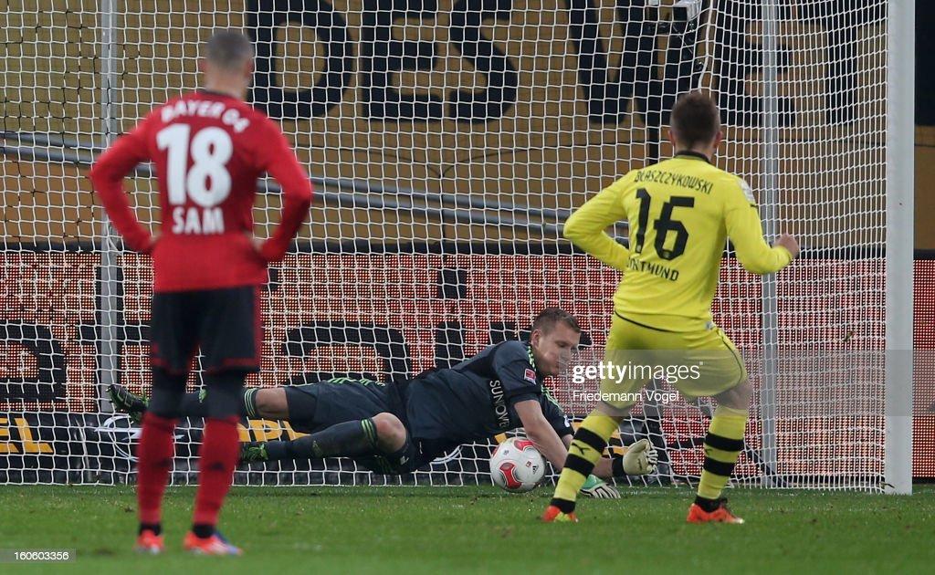 Bernd Leno (C) of Leverkusen saves the penalty from Jakub Kuba Blaszczykowski (R) of Dortmund battle for the ball during the Bundesliga match between Bayer 04 Leverkusen and Borussia Dortmund at BayArena on February 3, 2013 in Leverkusen, Germany.