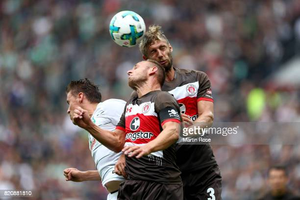 Bernd Nehrig and Lasse Sobiech of St Pauli and Max Kruse of Bremen head for the ball during the preseason friendly match between FC St Pauli and...