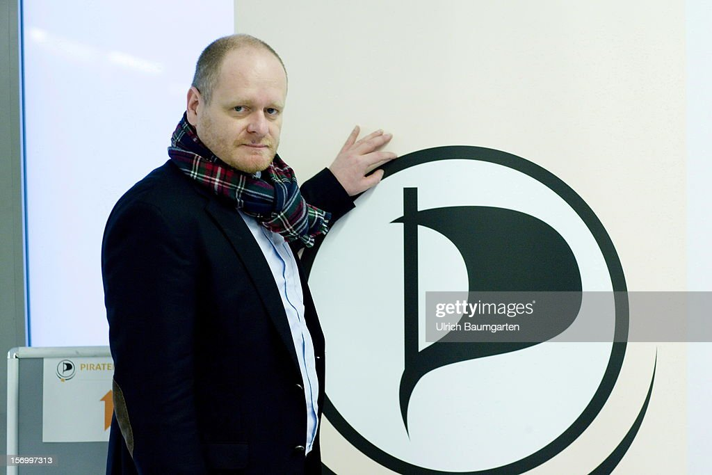 Bernd Schloemer, federal chairman of the Pirate party, in front of the party logo at the Pirate Party National Convention at RuhrCongress on November 24, 2012 in Bochum, Germany. German Pirates have a lot to achieve as the party is flagging in the polls and facing national elections in less than a year.