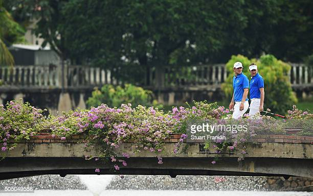 Bernd Wiesberger and Ian Poulter of team Europe walk over a bridge during the first day's fourball matches at the EurAsia Cup presented by DRBHICOM...