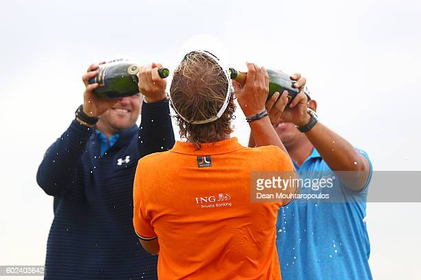 Bernd Wiesberger of Austria and Byeong Hun An of Korea pour champagne on Joost Luiten of the Netherlands as celebrates victory after the final round...