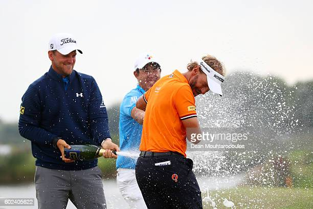Bernd Wiesberger of Austria and Byeong Hun An of Korea spray champagne on Joost Luiten of the Netherlands as celebrates victory after the final round...