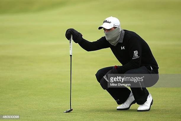 Bernd Wiesberger of Austria attempts to keep warm as he lines up a putt on the 15th green during the first round of the 144th Open Championship at...
