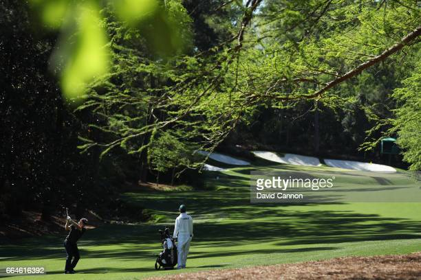 Bernhard Langer of Germany plays a shot on the 13th hole as caddie Terry Holt looks on during a practice round prior to the start of the 2017 Masters...