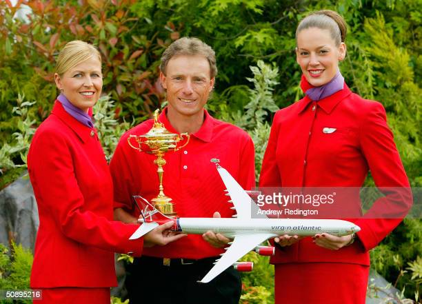 Bernhard Langer of Germany poses with the Ryder Cup trophy and two Virgin Airlines flight attendants during a Ryder Cup photocall at the Volvo PGA...