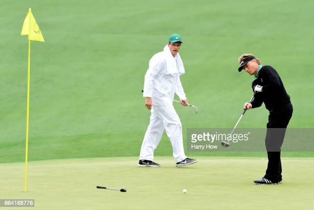 Bernhard Langer of Germany putts as his caddie looks on during a practice round prior to the start of the 2017 Masters Tournament at Augusta National...