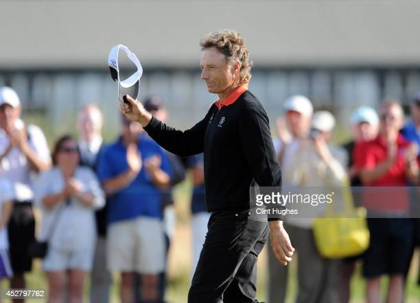 Bernhard Langer of Germany waves to the crowd as he walks up the fairway on the 18th hole during the fourth round of the Senior Open Championship at...
