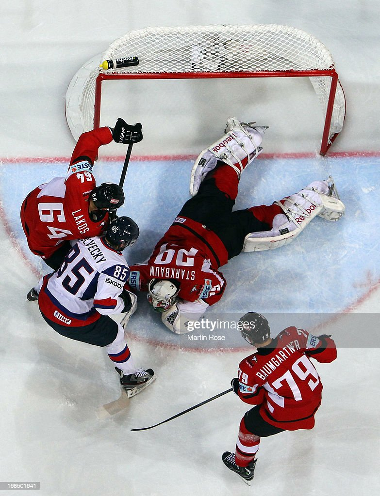 Bernhard Starkbaum (C), goaltender of Austria saves the shot of Peter Olvecky (#85) of Slovakia during the IIHF World Championship group H match between Slovakia and Austria at Hartwall Areena on May 10, 2013 in Helsinki, Finland.