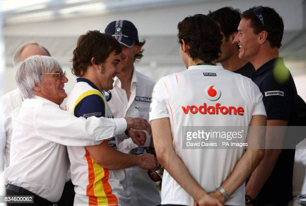 Bernie Ecclestone hugs Fernando Alonso after a meeting with some of the F1 drivers over the cost of their Super Licence during the qualifying session...