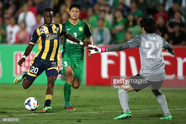 Bernie Ibini of the Mariners about to take a shot past Beijing Guoan goalkeeper Yang Zhi during the Asian Champions League match between the Central...