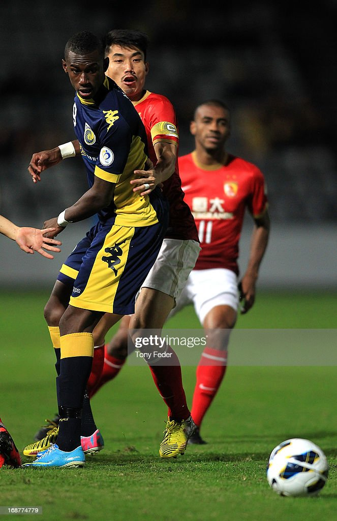 Bernie Ibini of the Mariners and Zheng Xiaoting of Evergrande contest the ball during the AFC Asian Champions League match between the Central Coast Mariners and Guangzhou Evergrande at Bluetongue Stadium on May 15, 2013 in Gosford, Australia.