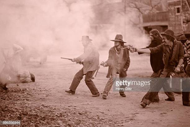Bernie Leadon and Glenn Frey stand among fellow Eagles dressed as outlaws battling it out with the law in a mock gunfight during the Desperado album...