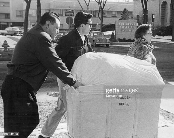 Bernie Medina left Ben G Martinez and Mrs Lucille W Smith all employees of Spalding House move a laundry basket to Children's Hospital E 19th Ave and...