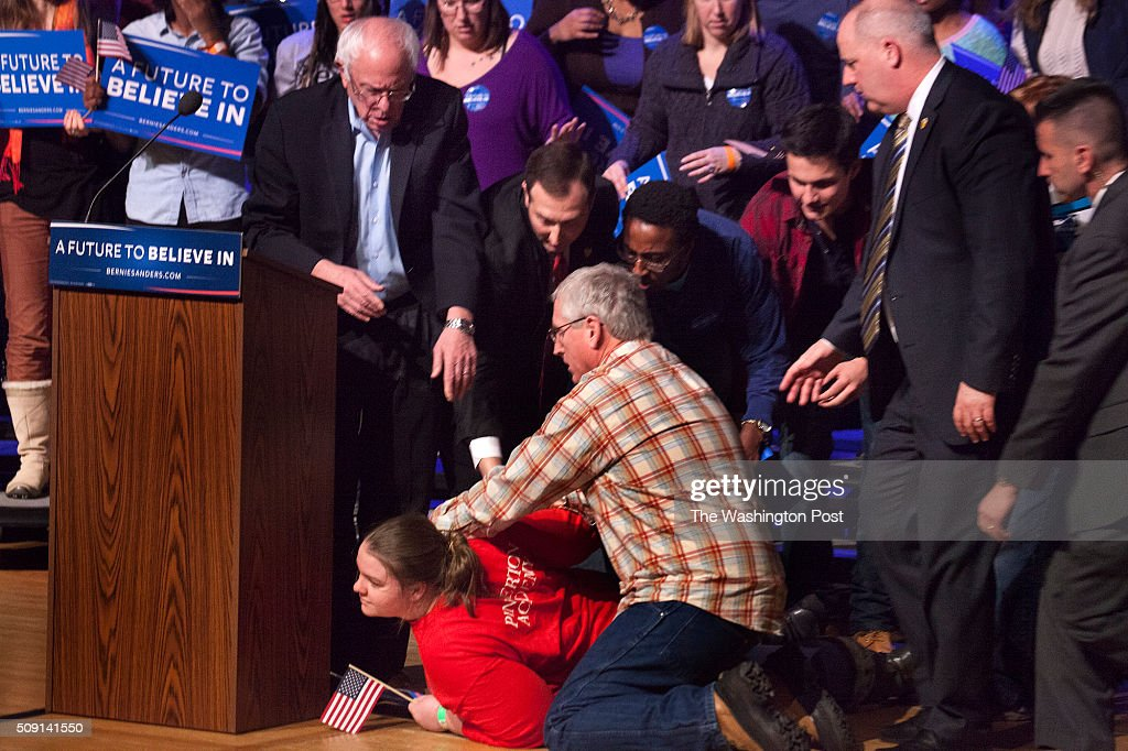 Bernie Sanders comes to the aid of one of his supporters who passed out and fell to the floor after standing behind him during his talk at Pinkerton Academy Stockbridge Theatre, 5 Pinkerton Street, Derry, NH
