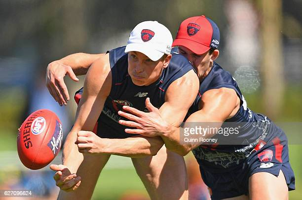 Bernie Vince of the Demons handballs whilst being tackled by Joel Smith during the Melbourne Demons AFL preseason training session at Gosch's Paddock...