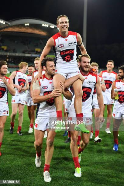 Bernie Vince of the Demons is chaired from the field by Cameron Pedersen and Jack Watts of the Demons during the round eight AFL match between the...