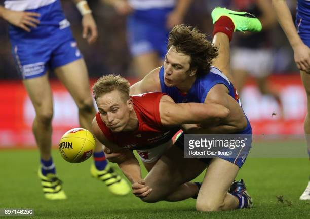 Bernie Vince of the Demons is challenged by Liam Picken of the Bulldogs during the round 13 AFL match between the Western Bulldogs and the Melbourne...