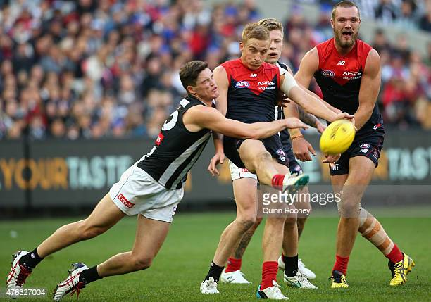 Bernie Vince of the Demons kicks whilst being tackled by Jack Crisp of the Magpies during the round 10 AFL match between the Melbourne Demons and the...