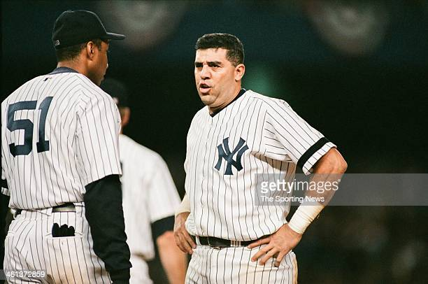 Bernie Williams and Luis Sojo of the New York Yankees talk during Game Three of the American League Division Series against the Oakland Athletics on...
